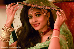 Bride in emerald green sangeet outfit.