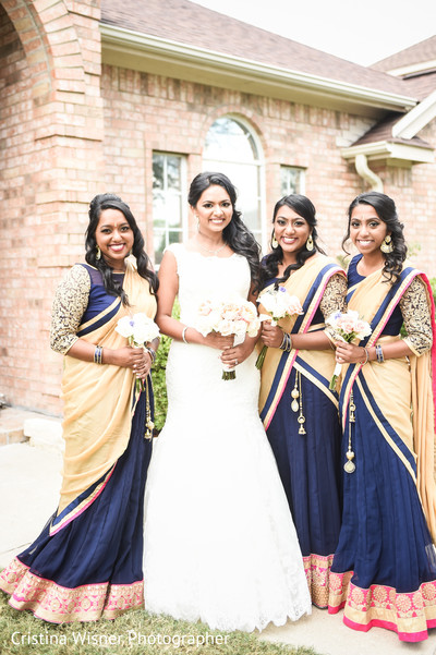 Maharani in white and bridesmaids in blue and yellow saris.
