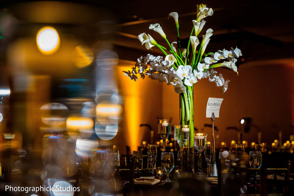 Tall wedding table centerpieces. in Virginia Fusion Wedding by Photographick Studios