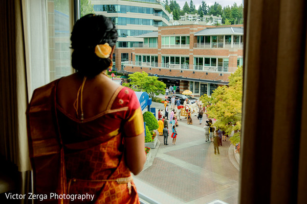 Indian bride takes a look at the baraat. in Kirkland, WA Indian Wedding by Victor Zerga Photography