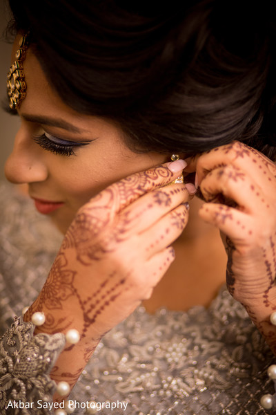 Maharani putting her earrings on in Falls Church, VA Indian Wedding by Akbar Sayed Photography