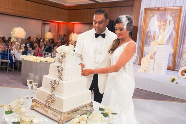 Cake cutting capture. in Westchester, New York Fusion Indian Wedding by Jay Seth Photography