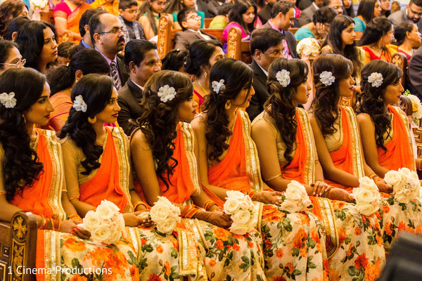Beautiful bridesmaids in orange flowered saris.