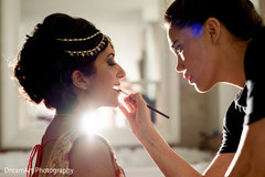 Makeup artist working on indian bride