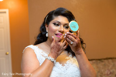 Bride takes a final look to her makeup.