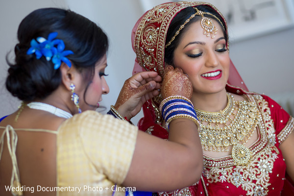 Indian bride trying her earrings before wedding ceremony