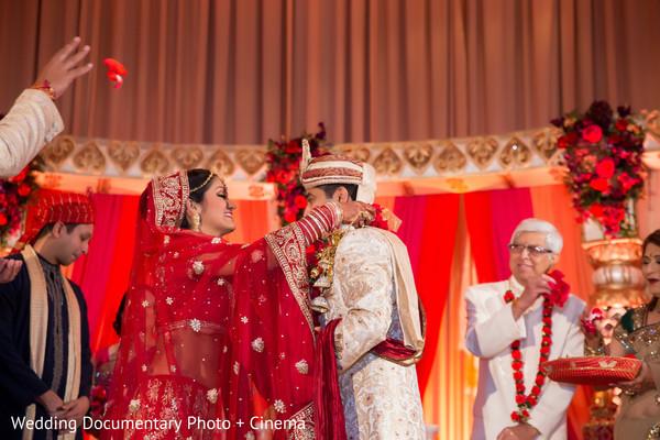 Indian bride adorns groom's neck at wedding ceremony