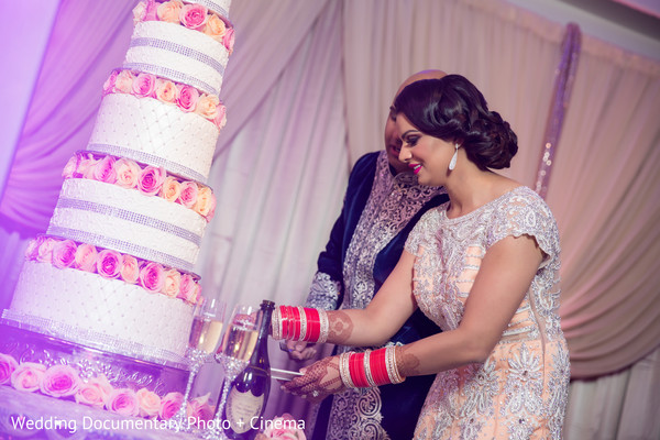 Indian bride cutting the cake at wedding reception