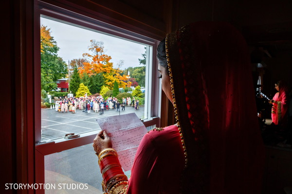 Bride reading the groom's letter. in New Rochelle, NY Sikh Wedding by StoryMotion Studios