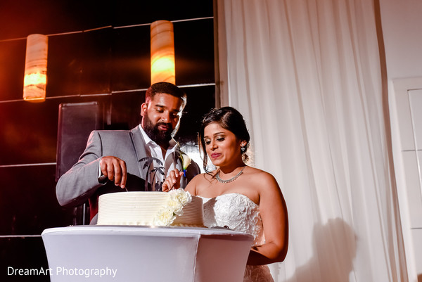 Indian couple cutting the cake at wedding reception in Playa Del Carmen, Mexico Wedding by DreamArt Photography