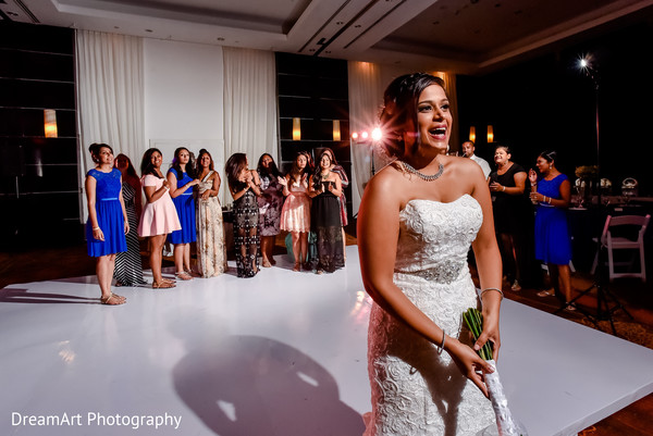 Indian bride about to throw the flower bouquet at wedding reception in Playa Del Carmen, Mexico Wedding by DreamArt Photography
