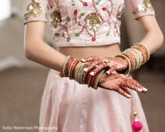 Indian bride showing her bangles and mehndi art photography