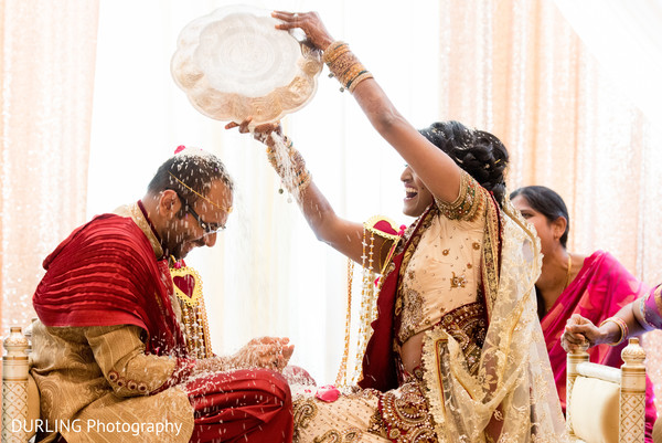 Indian bride throwing rice to the groom at wedding ceremony