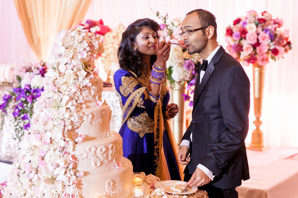 Indian couple eating cake at wedding reception