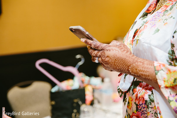 Indian bride texting on her phone before wedding ceremony