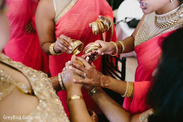 Indian bridesmaids helping the bride to get ready for wedding ceremony
