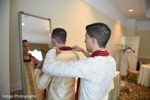 Groom being help to get ready.