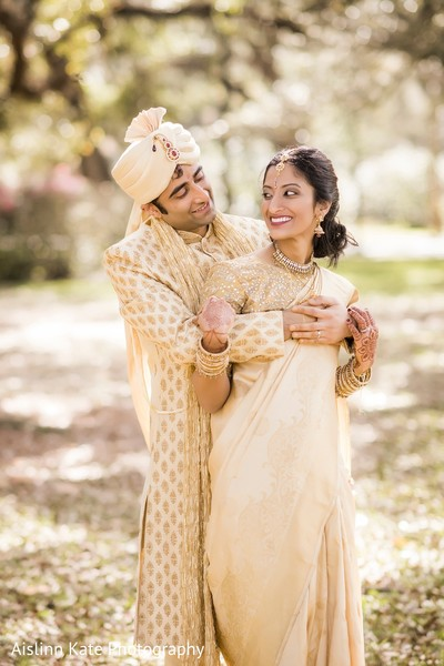 Indian bride and groom in gold cream wedding outfits.