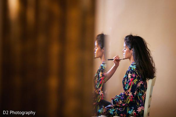 Makeup artist working on bride before wedding ceremony