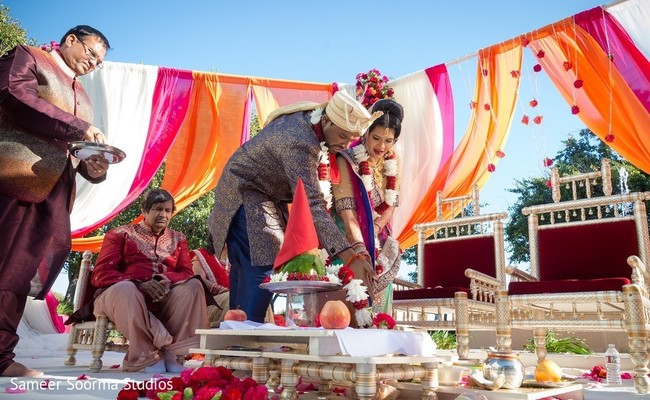 Couple lightning the sacred fire. in Redwood City Indian Wedding by Sameer Soorma Studios