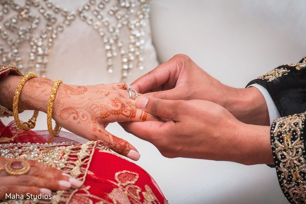 Indian groom putiing the ring on bride's hand at wedding ceremony