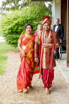 Indian groom walking down the aisle escorted by his mother.