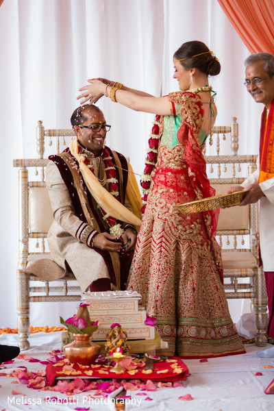 Indian bride tossing rose petals to groom during wedding ceremony