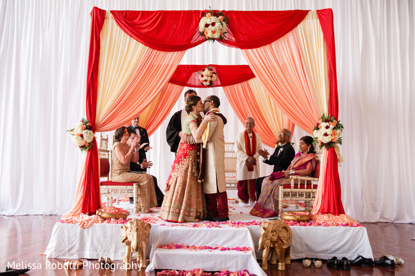 Indian bride and groom kissing during wedding ceremony