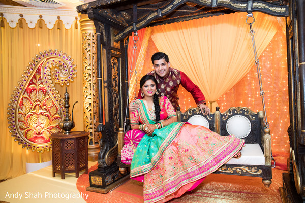 Indian couple posing on the stage swing.