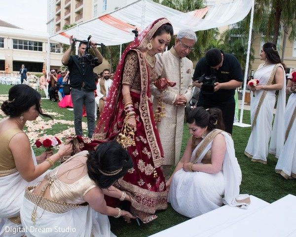 Indian bridesmaids helping bride to take shoes off