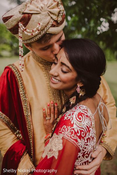 Indian groom kissing bride