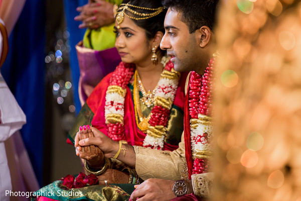 Indian groom holding bride's hand during wedding ceremony
