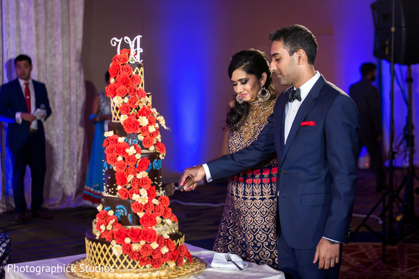 Indian bride and groom cutting the wedding cake