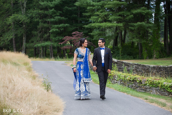 Glamorous Indian bride and groom in blue reception outfits.
