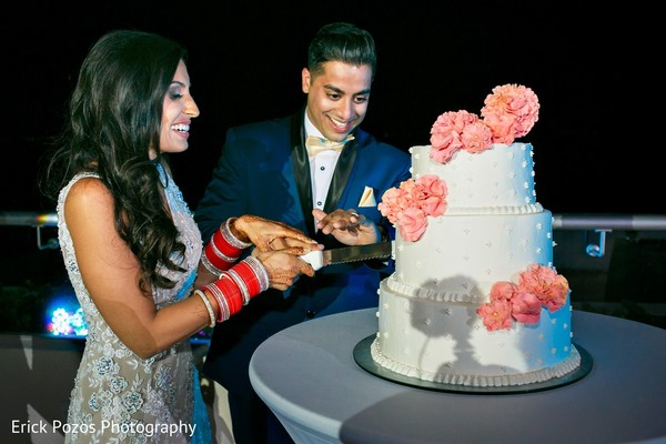 Indian bride and groom cutting the cake in Cancun, Mexico Destination Indian Wedding by Erick Pozos Photography