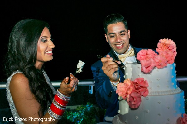 Indian bride and groom tasting the wedding cake in Cancun, Mexico Destination Indian Wedding by Erick Pozos Photography