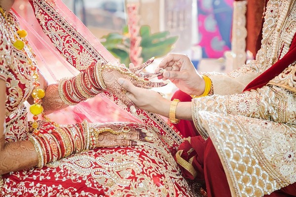 Indian groom putting wedding ring on bride in Jamaica, NY Indian Wedding by MaxPhoto NY