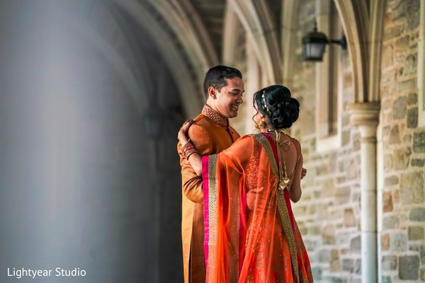 Indian bride and groom to be in matching orange outfits.