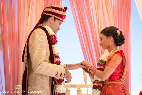 Indian bride putting wedding ring on groom