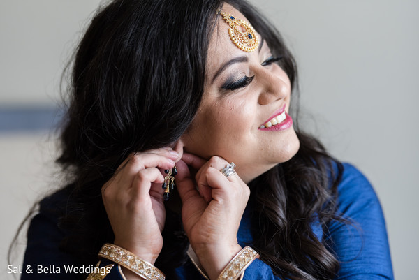 Beautiful indian bride putting on her earrings in Pittsburgh, PA Fusion Indian Wedding by Sal & Bella Weddings