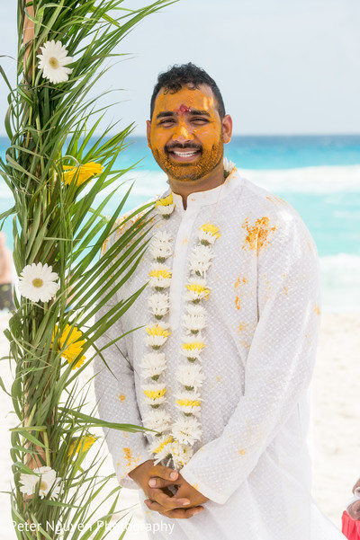 Indian groom painted with yellow tumeric paste
