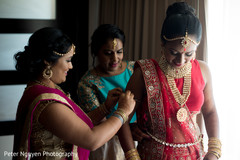 indian bride getting assistance with jewelry