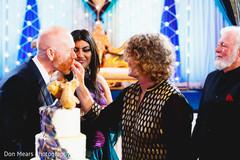 Indian groom tasting the wedding cake