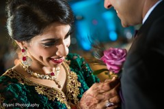 Indian bride helping groom with boutonniere