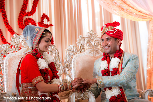 Lovely indian bride putting wedding ring on groom