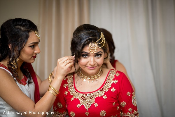 Indian bride getting help with jewelry