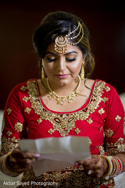 Beautiful indian bride reading letter from groom