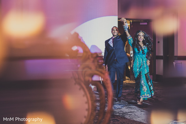 Upbeat indian couple making their entrance to wedding reception