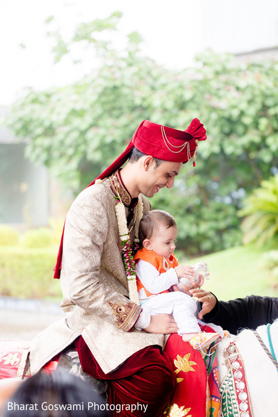Indian groom with little kid riding horse