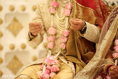 Indian groom holding bride's necklace